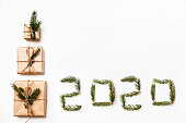 istock Christmas composition. Christmas gift boxes and 2020 made of fir branches. Flat lay, top view. 1195541839