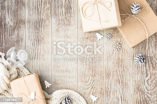 Christmas background with Christmas gift, knitted blanket, pine cones and decorations on wooden background