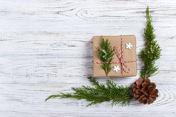 weihnachten-komposition. weihnachtsgeschenk, gestrickte decke, tannenzapfen, tannenzweigen auf hölzernen weißen hintergrund. flach legen, top aussicht - strickmantel stock-fotos und bilder