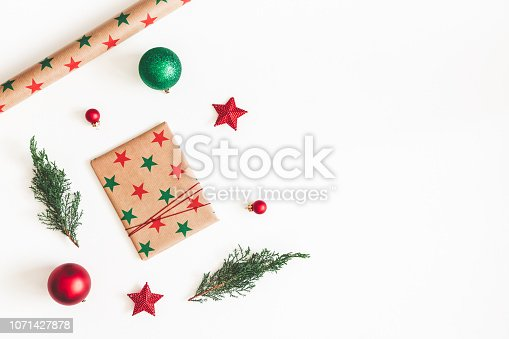 1074095098 istock photo Christmas composition. Christmas gift, pine branches, red and green decorations on white background. Flat lay, top view, copy space 1071427878
