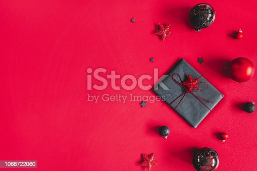 1062680370 istock photo Christmas composition. Christmas gift, red and black decorations on red background. Flat lay, top view, copy space 1068722060