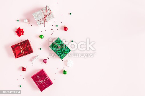 1060169304 istock photo Christmas composition. Christmas gifts, decorations on pastel pink background. Flat lay, top view, copy space 1071429984