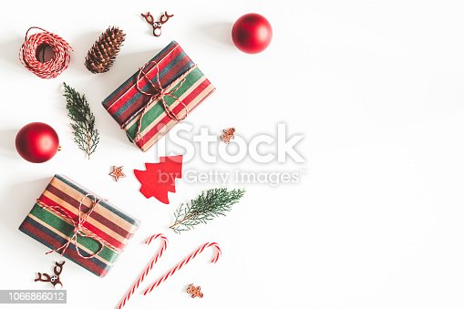 1074095098 istock photo Christmas composition. Christmas gifts, fir tree branches, decorations on white background. Flat lay, top view, copy space 1066866012