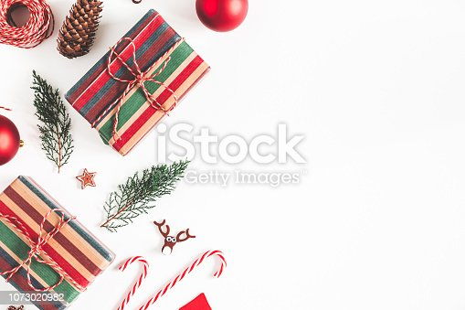 1074095098 istock photo Christmas composition. Christmas gifts, fir tree branches, decorations on white background. Flat lay, top view, copy space 1073020982