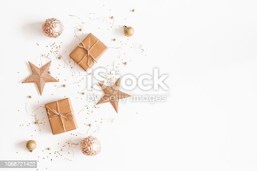 1076055746 istock photo Christmas composition. Christmas gifts, golden decorations on white background. Flat lay, top view, copy space 1068721422