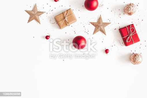 1076055746 istock photo Christmas composition. Christmas gifts, red and golden decorations on white background. Flat lay, top view, copy space 1066865698