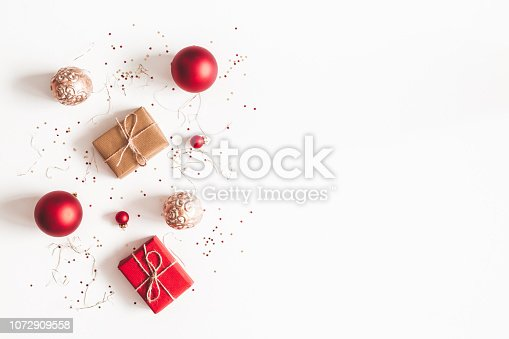 1076055746 istock photo Christmas composition. Christmas gifts, red and golden decorations on white background. Flat lay, top view, copy space 1072909558
