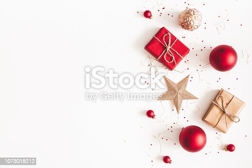 1060169304 istock photo Christmas composition. Christmas gifts, red and golden decorations on white background. Flat lay, top view, copy space 1073018212
