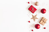 istock Christmas composition. Christmas gifts, red and golden decorations on white background. Flat lay, top view, copy space 1073018212