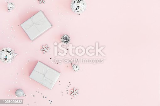 istock Christmas composition. Christmas gifts, silver decorations on pastel pink background. Flat lay, top view, copy space 1058029632