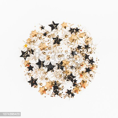 1062679964 istock photo Christmas composition. Christmas pattern made of golden and black decorations on white background. Flat lay, top view, square 1074395420