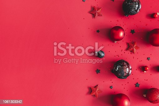 1062680370 istock photo Christmas composition. Christmas red and black decorations on red background. Flat lay, top view, copy space 1061303342