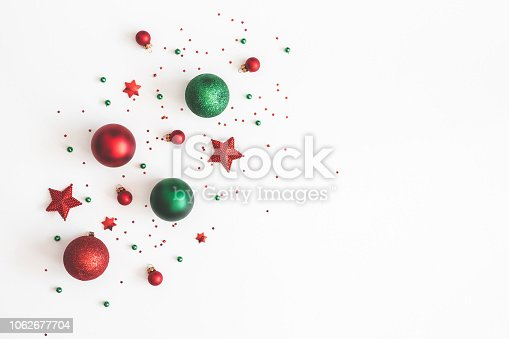 istock Christmas composition. Christmas red and green decorations on white background. Flat lay, top view, copy space 1062677704