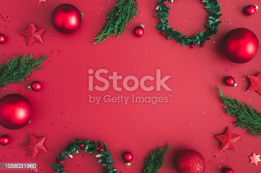 1062680370 istock photo Christmas composition. Christmas red decorations, fir tree branches on red background. Flat lay, top view, copy space 1058031960