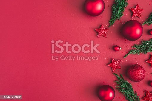1062680370 istock photo Christmas composition. Christmas red decorations, fir tree branches on red background. Flat lay, top view, copy space 1060170182