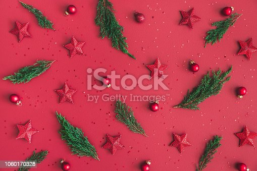 1062680370 istock photo Christmas composition. Christmas red decorations, fir tree branches on red background. Flat lay, top view 1060170328