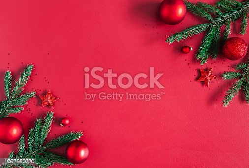 1062680370 istock photo Christmas composition. Christmas red decorations, fir tree branches on red background. Flat lay, top view, copy space 1062680370