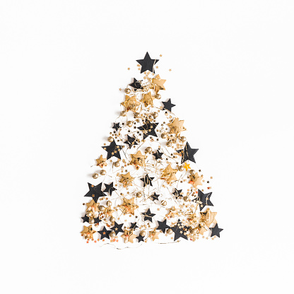 Christmas composition. Christmas tree made of golden and black decorations on white background. Flat lay, top view, square