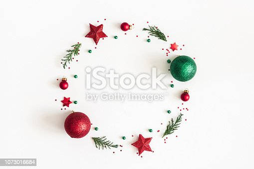 istock Christmas composition. Christmas wreath made of decorations, fir tree branches on white background. Flat lay, top view, copy space 1073016684