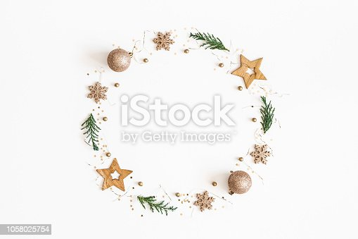 1062679964 istock photo Christmas composition. Christmas wreath made of golden decorations, fir tree branches on white background. Flat lay, top view, copy space 1058025754