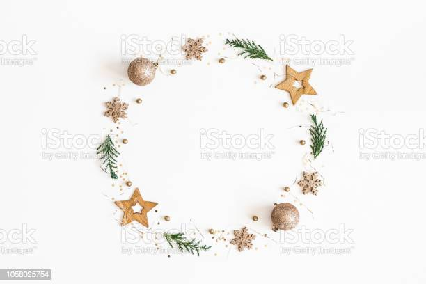 Photo of Christmas composition. Christmas wreath made of golden decorations, fir tree branches on white background. Flat lay, top view, copy space