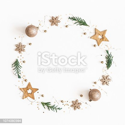 istock Christmas composition. Christmas wreath made of golden decorations, fir tree branches on white background. Flat lay, top view, copy space, square 1074092394