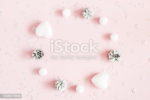 istock Christmas composition. Christmas wreath made of pink and white decorations on pastel pink background. Flat lay, top view, copy space 1058025940