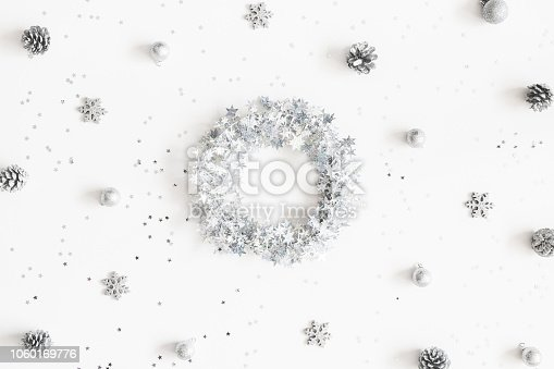1074095098 istock photo Christmas composition. Christmas wreath made of silver decorations on white background. Flat lay, top view 1060169776