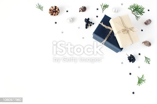 Christmas composition. Decorative corner, banner made of cypress branches, pine cones, christmas wrapped gifts, black berries and silver confetti stars, white table background. Flat lay, top view.
