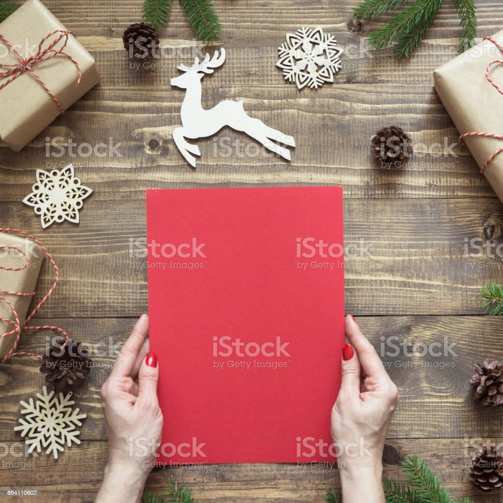 Christmas composition. Empty blank letter for Santa or your wishlist or advent activities in female hand. Top view. royalty-free stock photo