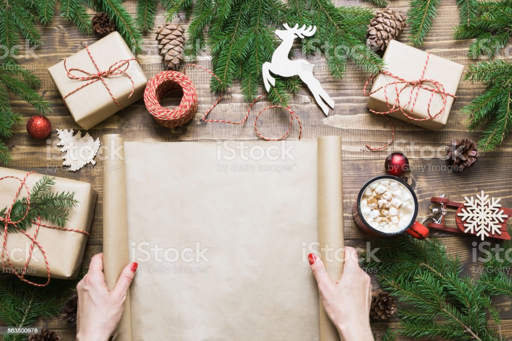 Christmas composition. Female holding empty scroll wishlist for Santa...