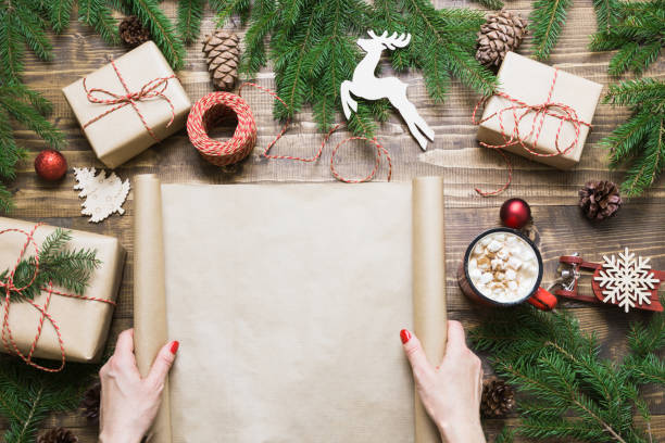 christmas composition. female holding empty scroll wishlist for santa claus or holiday cheers laid on a wooden table with christmas giftbox and decor. flat lay, top view, copy space. - wrapping paper stock photos and pictures