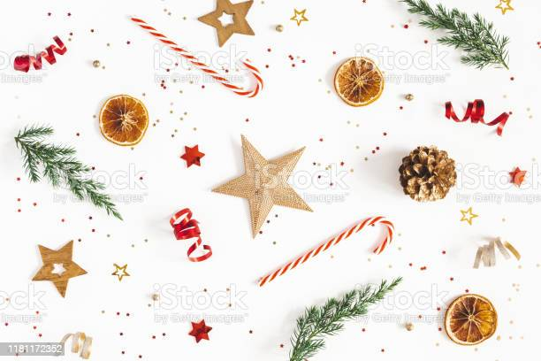 Photo of Christmas composition. Fir tree branches, golden and red decorations on white background. Christmas, winter, new year concept. Flat lay, top view