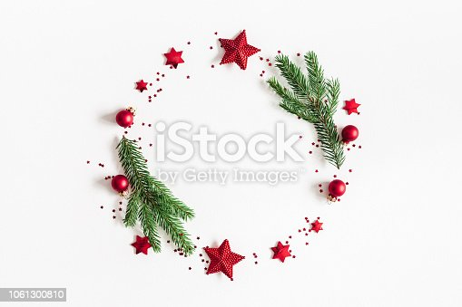 1060169304 istock photo Christmas composition. Fir tree branches, red and green decorations on white background. Christmas, winter, new year concept. Flat lay, top view, copy space 1061300810