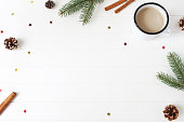 istock Christmas composition. Frame made of fir, spruce branches, pine cones, cinnamon sticks and glittering confetti stars on white wooden table background. Coffee in enamel mug. Flat lay, top view. 1034724814