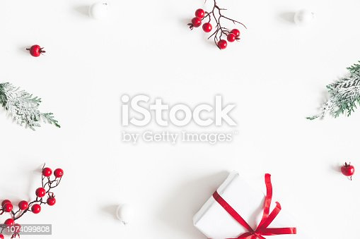 1076057502 istock photo Christmas composition. Frame made of gift, snowflakes, fir tree branches and red berries on white background. Christmas, winter, new year concept. Flat lay, top view, copy space 1074099808