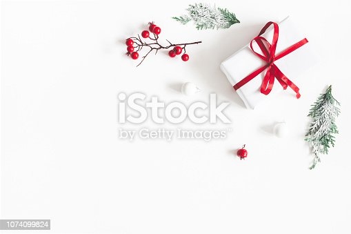 1076055746 istock photo Christmas composition. Frame made of gift, snowflakes, fir tree branches and red berries on white background. Christmas, winter, new year concept. Flat lay, top view, copy space 1074099824