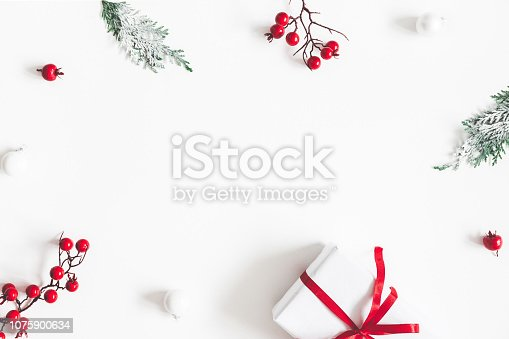 1076057502 istock photo Christmas composition. Frame made of gift, snowflakes, fir tree branches and red berries on white background. Christmas, winter, new year concept. Flat lay, top view, copy space 1075900634