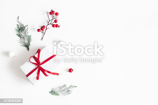 istock Christmas composition. Frame made of gift, snowflakes, fir tree branches and red berries on white background. Christmas, winter, new year concept. Flat lay, top view, copy space 1076063382