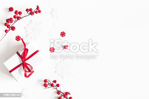 1064023690 istock photo Christmas composition. Frame made of gift, snowflakes, red berries on white background. Christmas, winter, new year concept. Flat lay, top view, copy space 1080168142