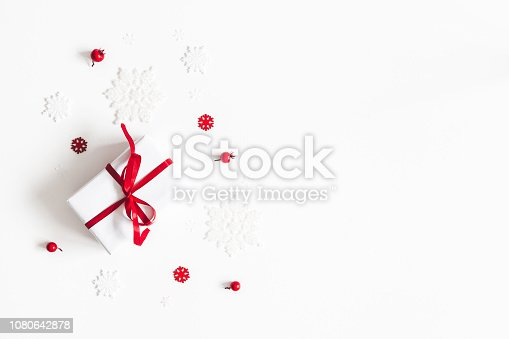 1064023690 istock photo Christmas composition. Frame made of gift, snowflakes, red berries on white background. Christmas, winter, new year concept. Flat lay, top view, copy space 1080642878