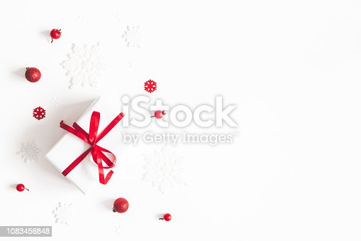 1064023690 istock photo Christmas composition. Frame made of gift, snowflakes, red berries on white background. Christmas, winter, new year concept. Flat lay, top view, copy space 1083456848