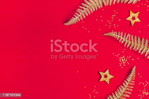 1062680370 istock photo Christmas composition. Frame made of golden decorations on red background. Christmas, winter, new year concept. Flat lay, top view, copy space 1187101344