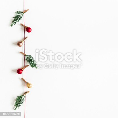 1074095098 istock photo Christmas composition. Garland made of red and golden balls, fir tree branches on white background. Christmas, winter, new year concept. Flat lay, top view, copy space, square 1072910756
