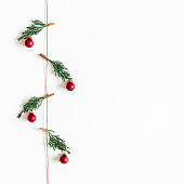 istock Christmas composition. Garland made of red and golden balls, fir tree branches on white background. Christmas, winter, new year concept. Flat lay, top view, copy space, square 1076057206