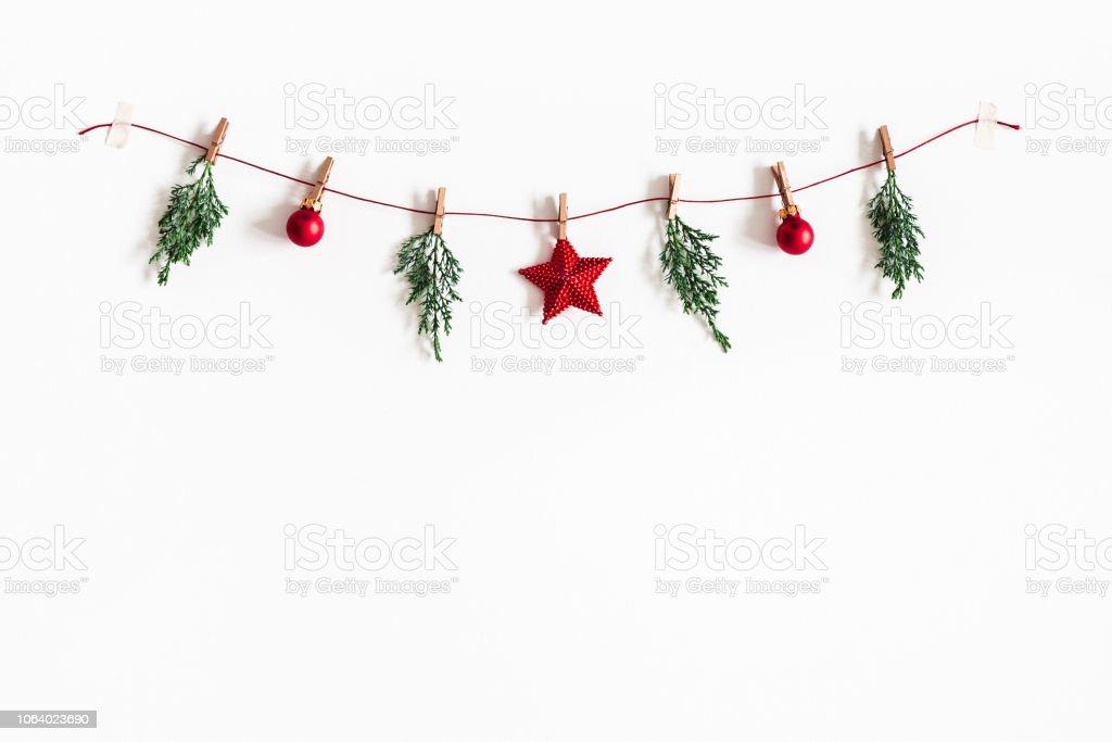 Christmas sammansättning. Garland tillverkad av röda bollar och fir trädgrenar på vit bakgrund. Jul, vinter, nytt år koncept. Platt lekmanna, top view, kopia utrymme - Royaltyfri 2019 Bildbanksbilder