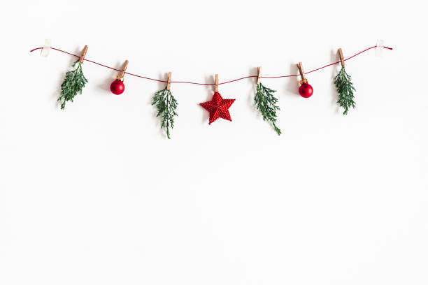 Christmas composition. Garland made of red balls and fir tree branches on white background. Christmas, winter, new year concept. Flat lay, top view, copy space stock photo