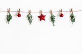 istock Christmas composition. Garland made of red balls and fir tree branches on white background. Christmas, winter, new year concept. Flat lay, top view, copy space 1072910616