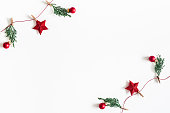 istock Christmas composition. Garland made of red balls and fir tree branches on white background. Christmas, winter, new year concept. Flat lay, top view, copy space 1076057502