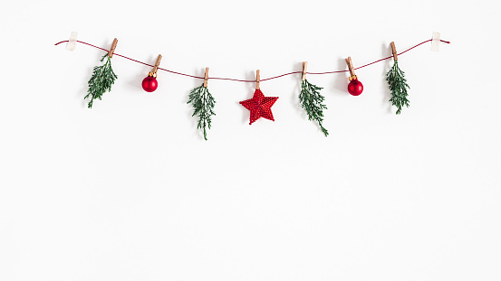 Christmas composition. Garland made of red balls and fir tree branches on white background. Christmas, winter, new year concept. Flat lay, top view